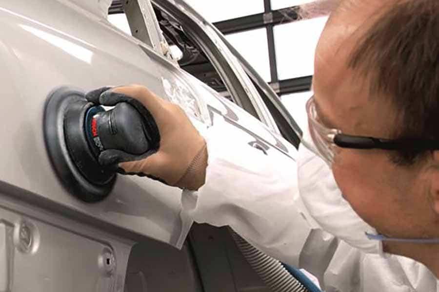 hombre trabajando en taller con herramientas neumaticas bosch