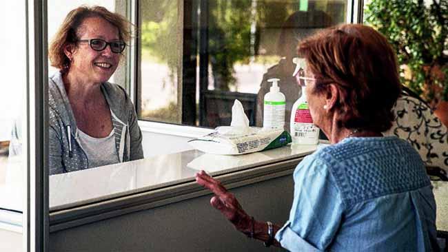 mujeres hablan en mostrador con pantalla