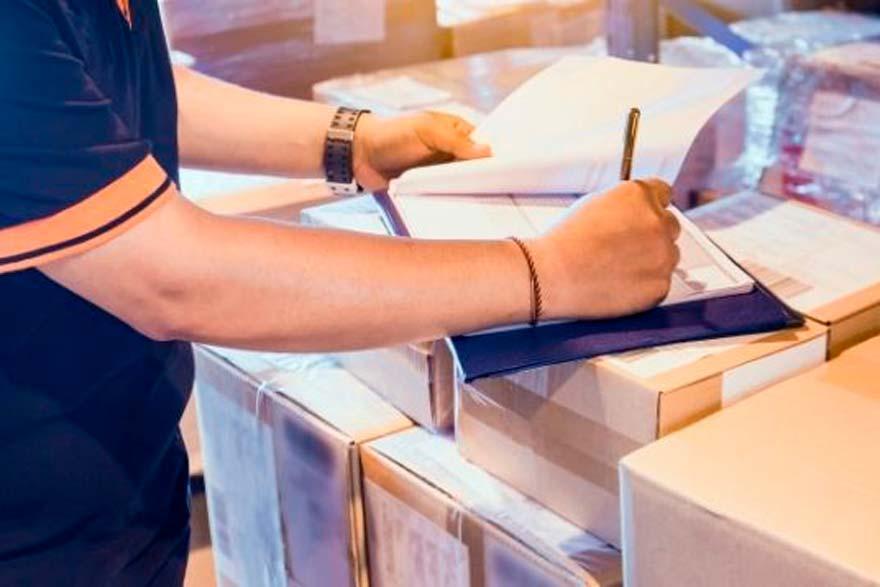 Persona anotando encima de unas cajas